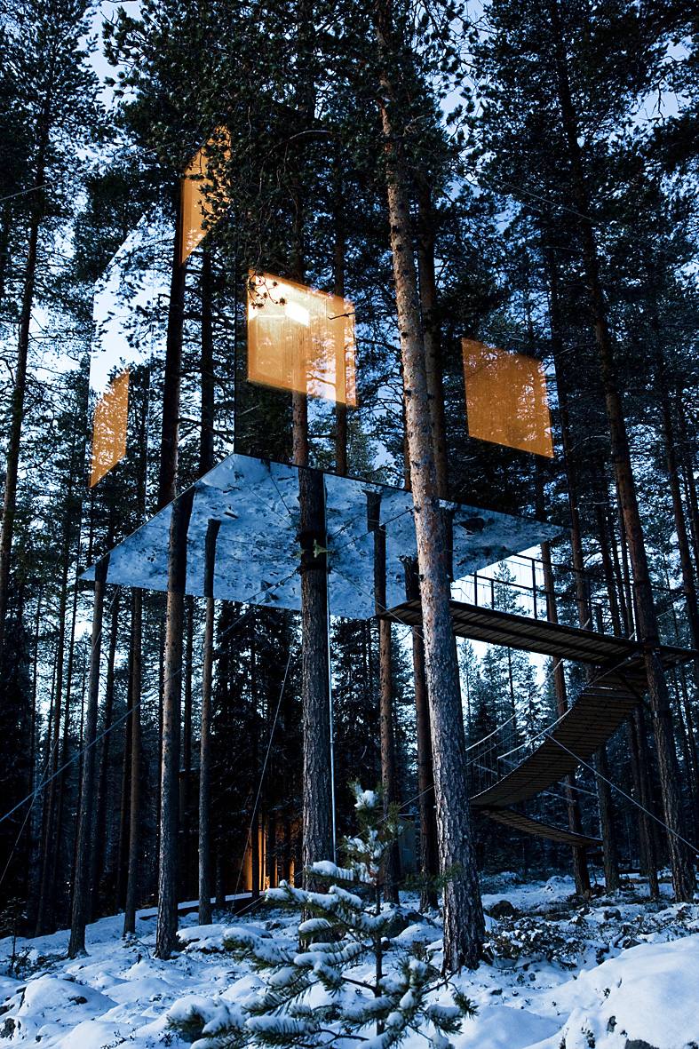 reflecting mirror tree house with low lights and surrounded buy snowy trees