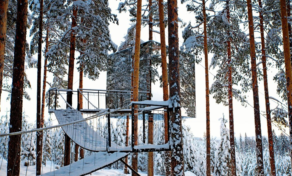 suspended wooden path leading to the mirror tree house covered in snow