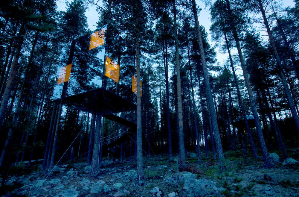 mirror cube tree house at nighttime with bright windows
