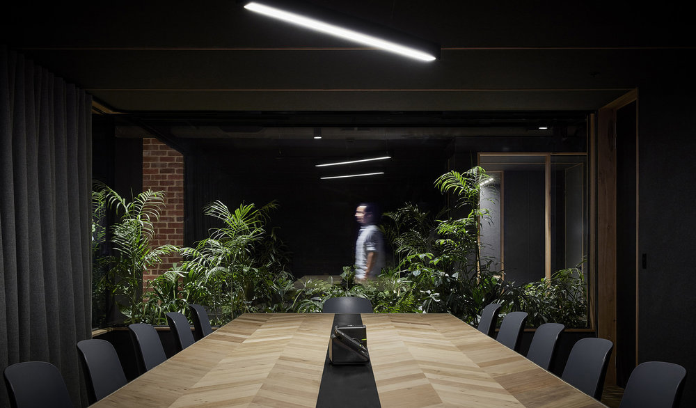 long wooden table in meeting room with plant screen