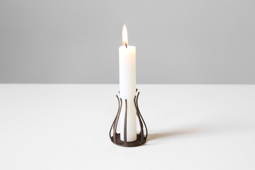 Design candle holder with burning candle by kamp studio