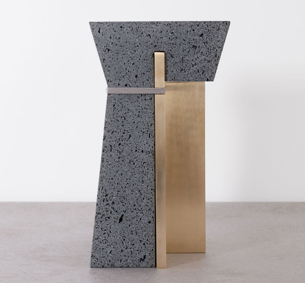 Frontal view of the lava rock stool with brass detail by formafantasma