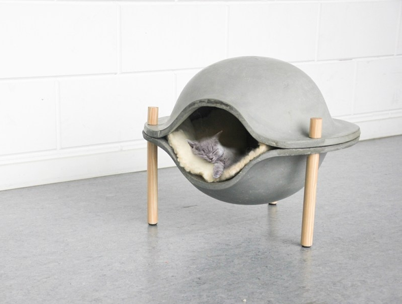 A futuristic and minimal concrete ball with wooden legs designed by  Geerke Sticker .