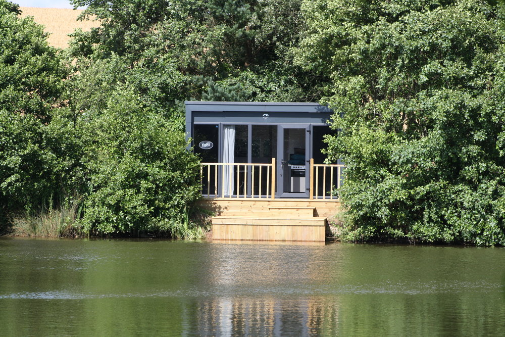 Kingfisher - Fully fitted cabin includes bathroom with shower and toilet, living room with sofa that turns into super comfy double bed, TV, kitchen fitted with grill, gas hob, sink, microwave and fridge..Comes with all linen & towelsOutside space includes private hot tub, table and chairs and relaxing furniture for 2 plus BBQ areaSpecimen Carp fishing from deck permitted