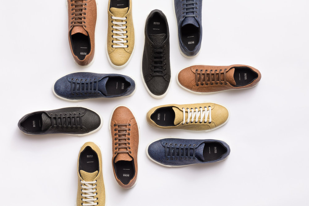 May 2018 – HUGO BOSS launches a new BOSS Menswear shoe produced with Piñatex, a natural-based material made of pineapple leaf fibers by Ananas Anam. The project is part of the commitment to innovation across the Company's offering as well as the continuous search for more sustainable ways to design, source and produce.      Harvested as a by-product of existing agriculture, the pineapple leaves require no extra resources to grow, furthermore providing farming communities with an additional income. The textile is colored using natural plant-based dyes. In combination with a recycled TPU sole, the shoe is 100% vegan and designed to make a minimal impact on our planet.      Available in four colors, the vegan shoes are presented in a fully recyclable and biodegradable paper box, made from 100% recovered fibers and are sold in selected BOSS retail stores worldwide as well as in the    HUGO BOSS online store   .