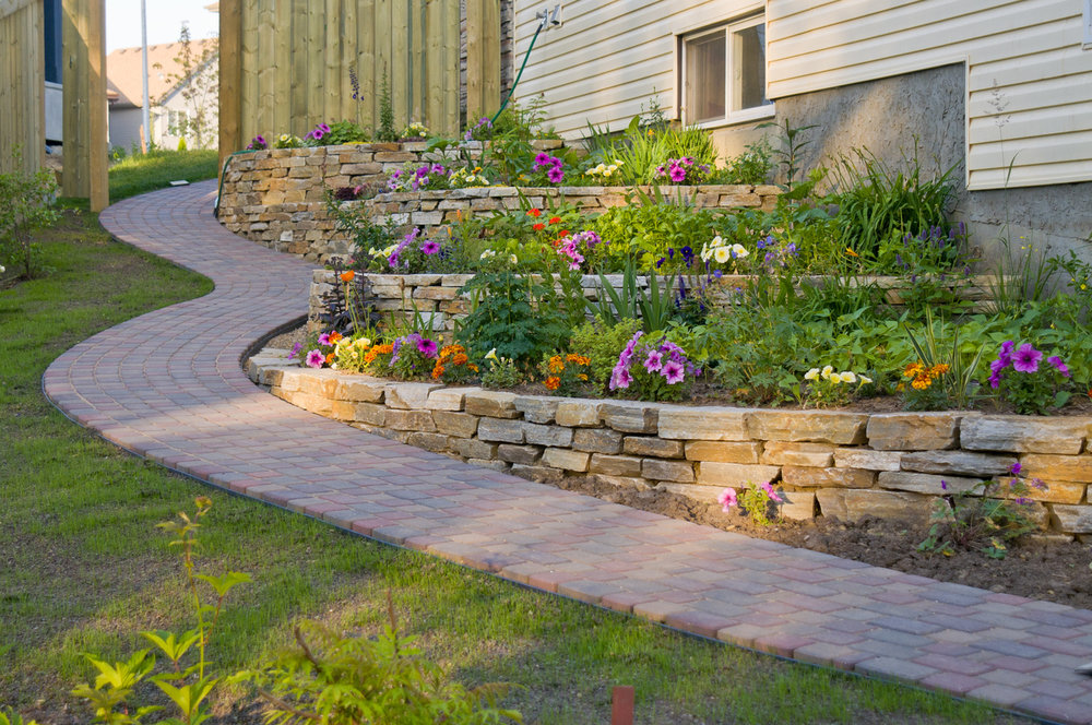 Retaining Wall's - Retaining walls can create dimension in slopes with beautiful tiered garden beds. They can also be used to correct grading issues and provide a new aesthetic to a patio or outdoor kitchen.