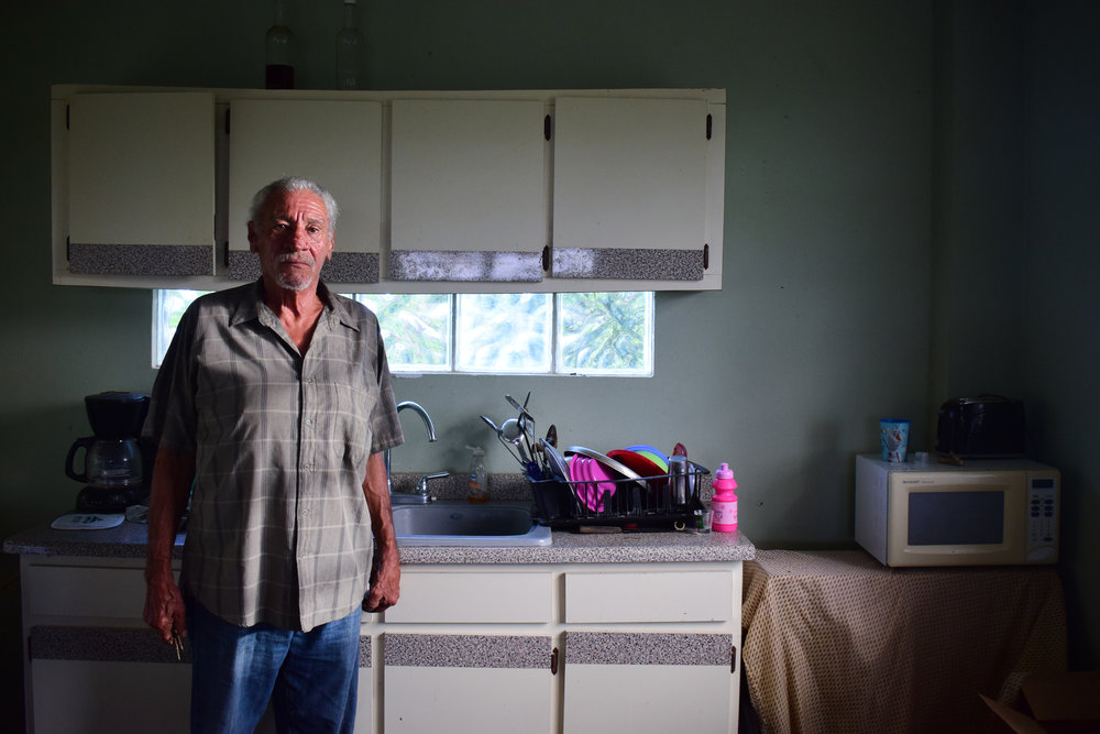 Adalberto Santiago stands in the kitchen of his home in Yabucoa, without power nearly nine months after Hurricane Maria.