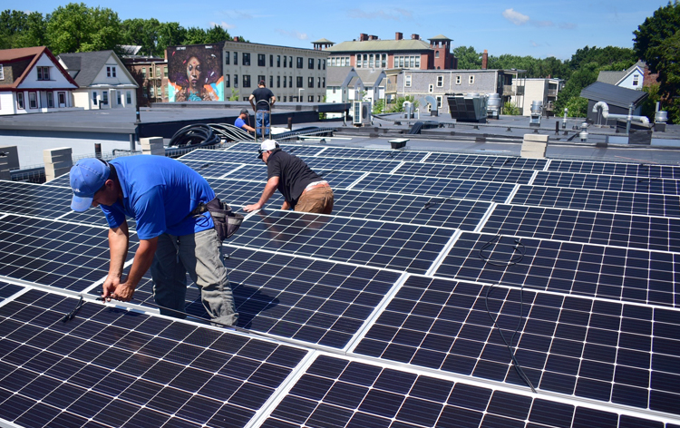 Installing solar panels on this Dorchester rooftop creates green jobs with a local, immigrant-owned solar installer, rooftop lease income to a local nonprofit organization and renewable energy credits for the City of Somerville. (Photo by Cody Eaton)