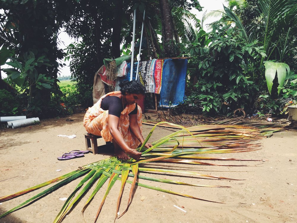 Woman weaving palm frond for a thatched roof in Kochi, Kerala. Photo by, Mary Elizabeth Heard