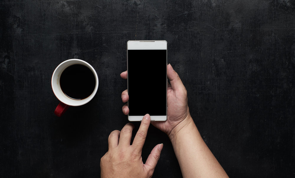 graphicstock-hand-using-phone-black-screen-with-cup-of-coffee-wooden-black-office-desk-table-on-top-view_BOzEFjvgjl.jpg