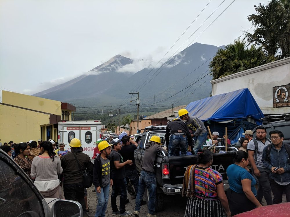 Locals, volunteers and first responders at Alotenango where survivors take refuge. Fuego volcano smoking in the background.