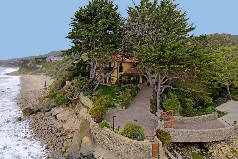 This jewel box of a Malibu home is located within a secluded cove and enjoys a creekside meditation deck.