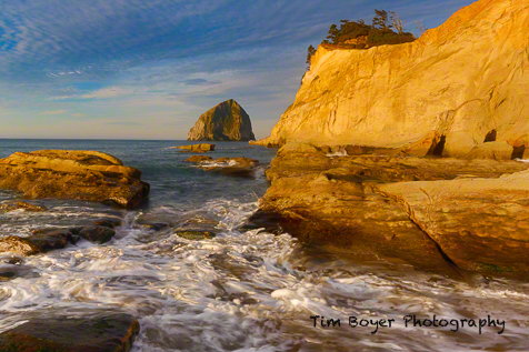Haystack Rock and the golden sandstone of Cape Kiwanda in full morning light.