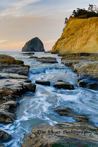 Haystack Rock and the golden sandstone of Cape Kiwanda at sunrise.