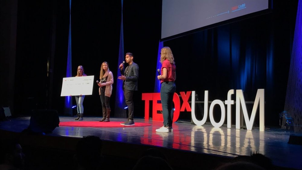Payton Watt (center left) and Hussain Ali (center right) accepting the Award for Innovation in front of the TEDxUofM audience.