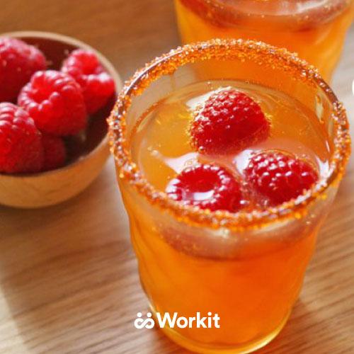 orange mocktail with cranberry garnish and sugar on the glass rim