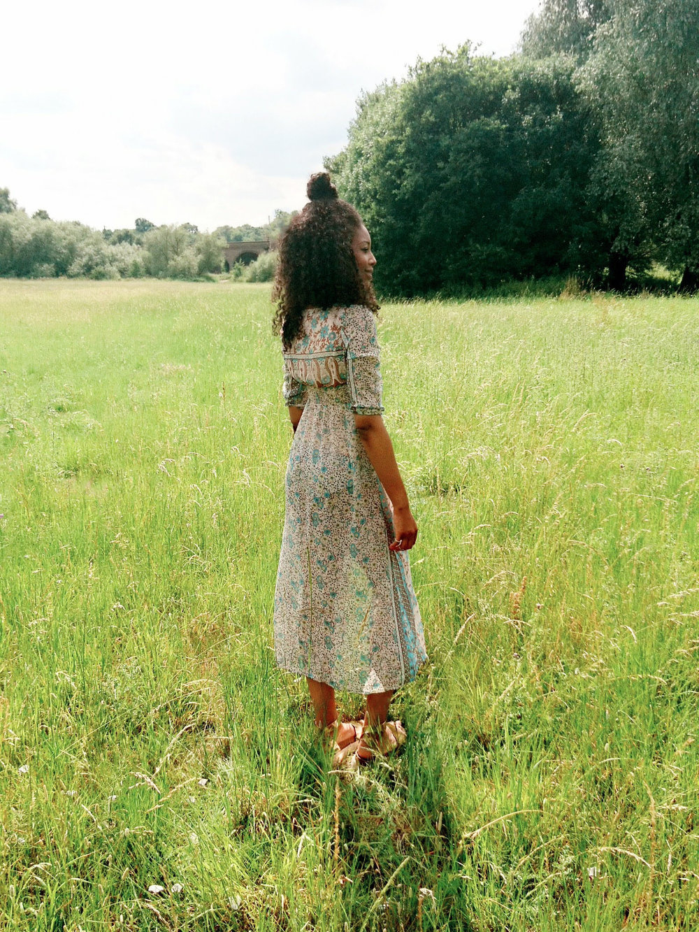 Curly hair, green maxi dress, rose gold vegan leather sandals