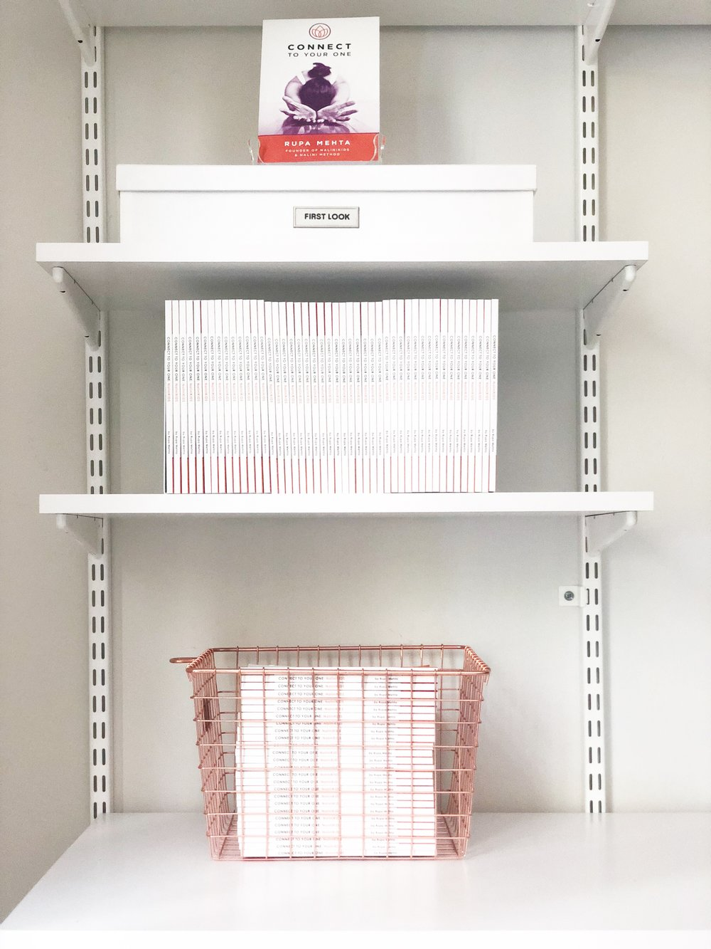 BOOKENDS ARE YOUR FRIENDS - Bookends are used to hold books upright on the shelves. I love these bookends from The Container Store because they have a slim profile and create a floating look. You can't even see them!The white document box matches the magazine file boxes we used earlier and this amazing Copper basket I found at Home Goods holds extra copies of books. The open basket makes it easy for Rupa and her team to grab books on the go and still keeps things stylish.
