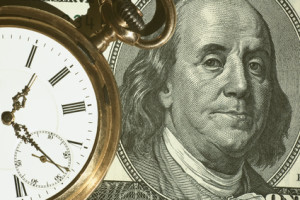 Time and Money concept image. us currency and a pocket watch portray time and money.Business concept.