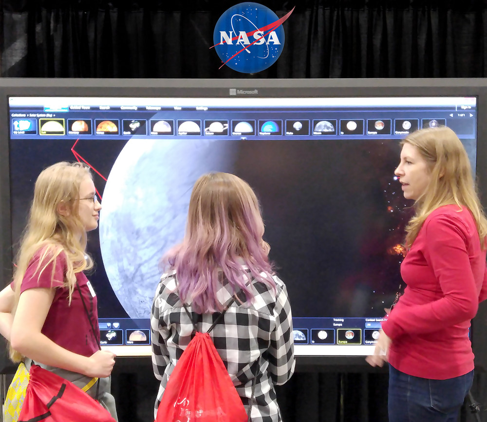 A subject expert demonstrates Jupiter's moon, Europa, in the World Wide Telescope application to visitors at the Science and Engineering Festival.