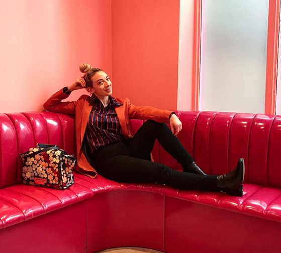 Bex sitting on a couch dressed in office clothes