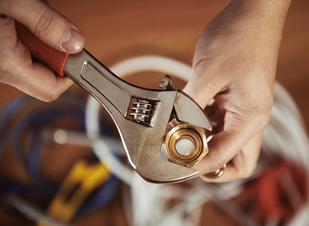 Hands holding wrench around bolt