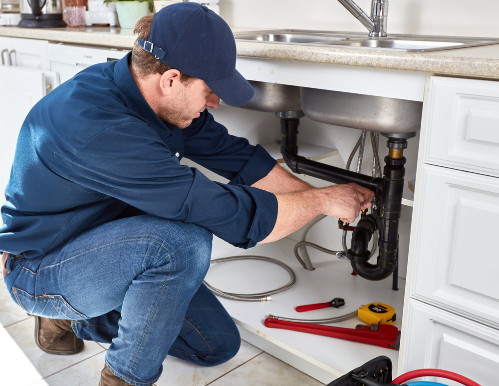 Repairman working under kitchen sink