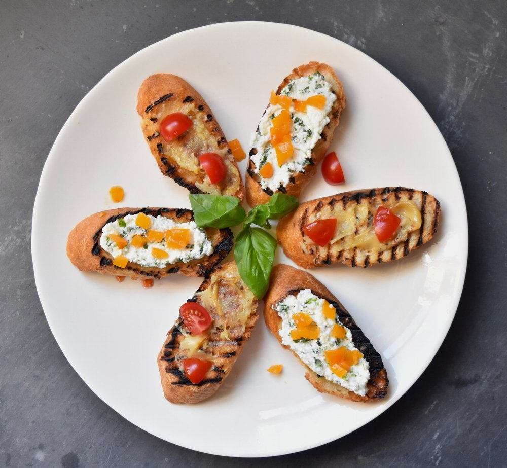 Brush sliced baguettes with herb oil, grill to toast, and top with herbed ricotta, roasted garlic, and tomatoes.