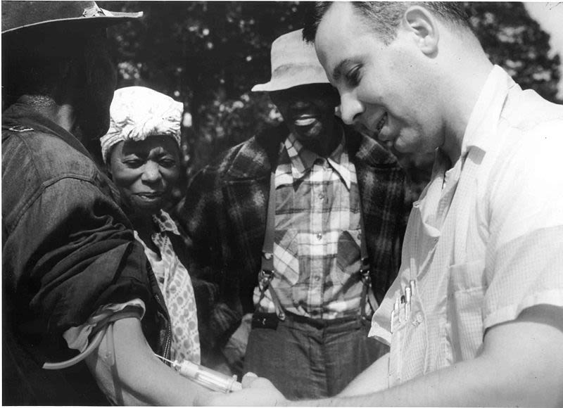 "Tuskegee syphilis experiment, one of many similar experiments on Black and Central American people to test the efficacy of syphilis treatment. Victims were lied to about the nature of the experiments. The above depicted people were told they were being treated for ""bad blood."""