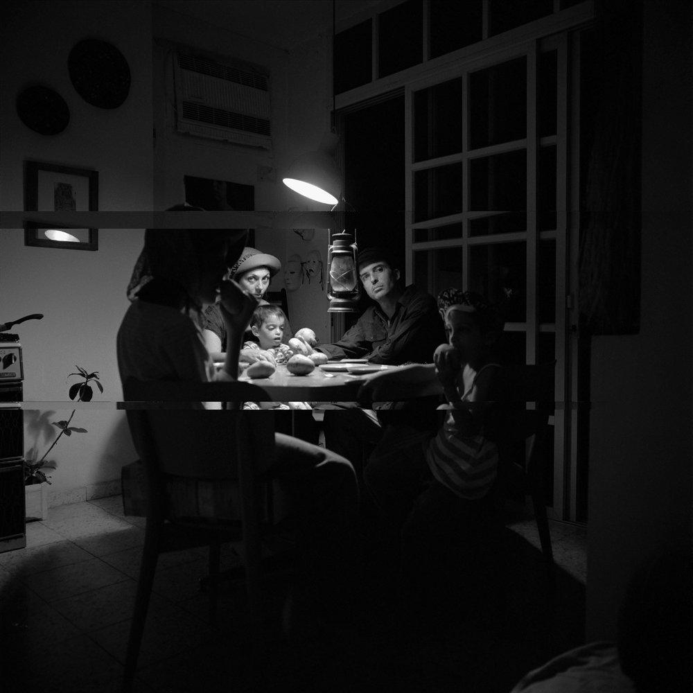 """בועז טל, דיוקן עצמי עם המשפחה - אוכלי תפוחי האדמה, מחווה לוואן גוך. 1990. תצלום שחור לבן, 100x100ס""""מ."""