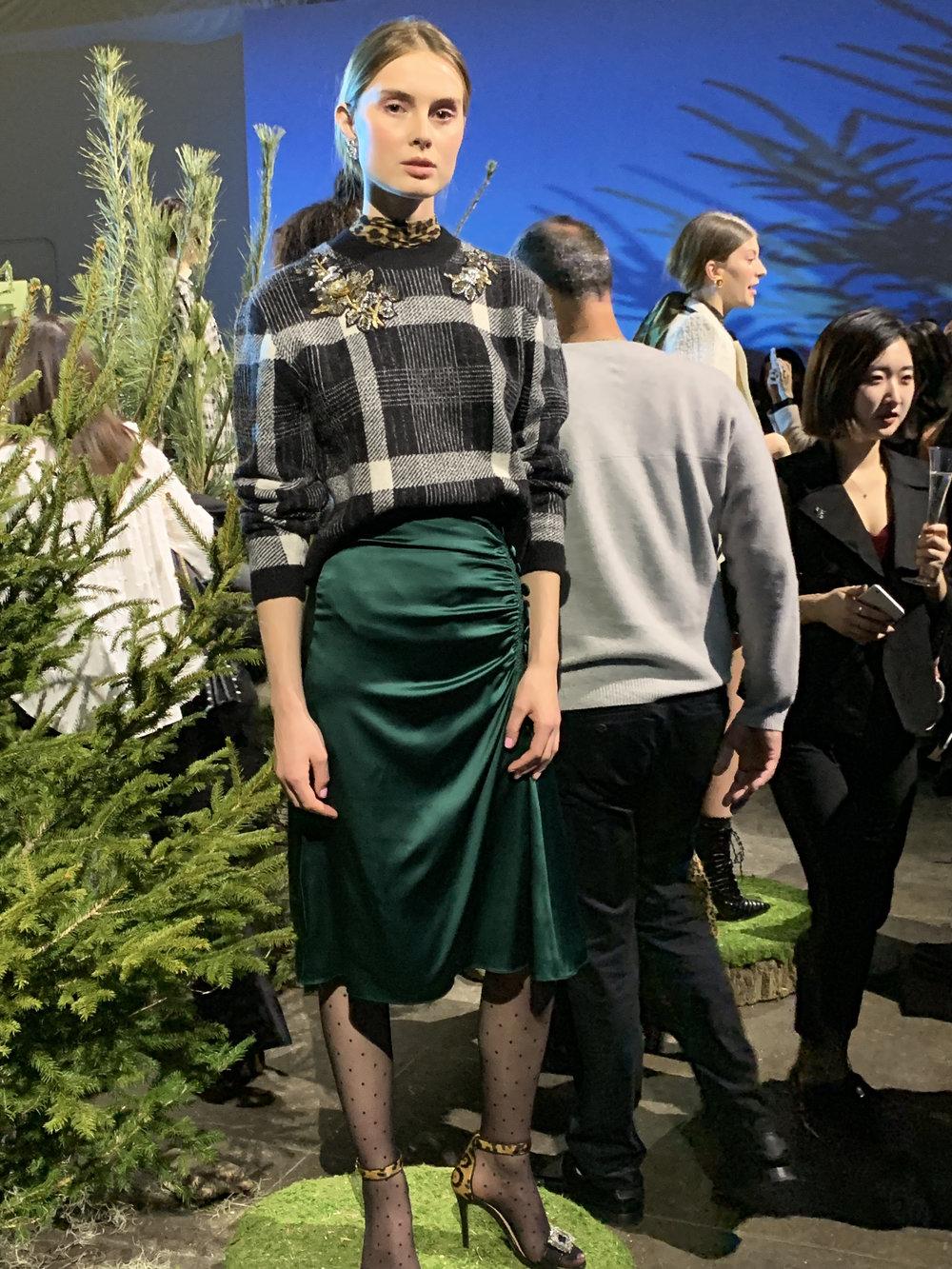 Model is wearing: Leopard KANU Top, Plaid DEANA Sweater, Green MINETTA Skirt, Leopard/Black ROAN Sandals