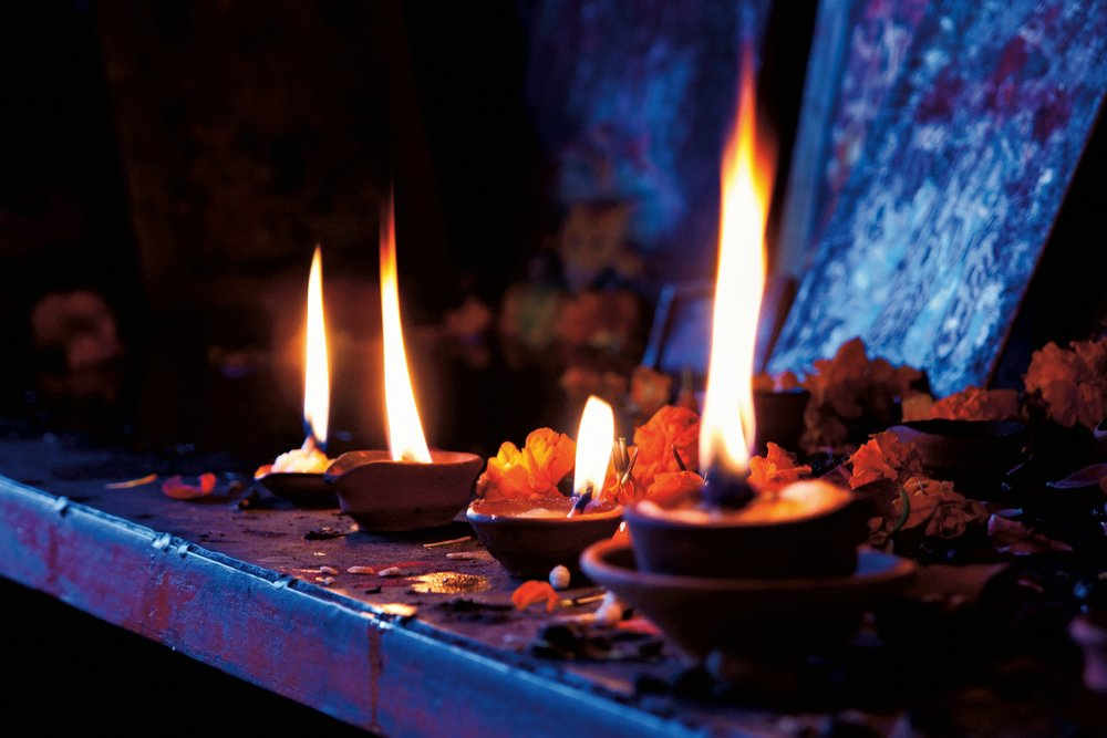 Three flames burn tall our of small terra cotta candle holders amid orange flowers strewn on a blue table.