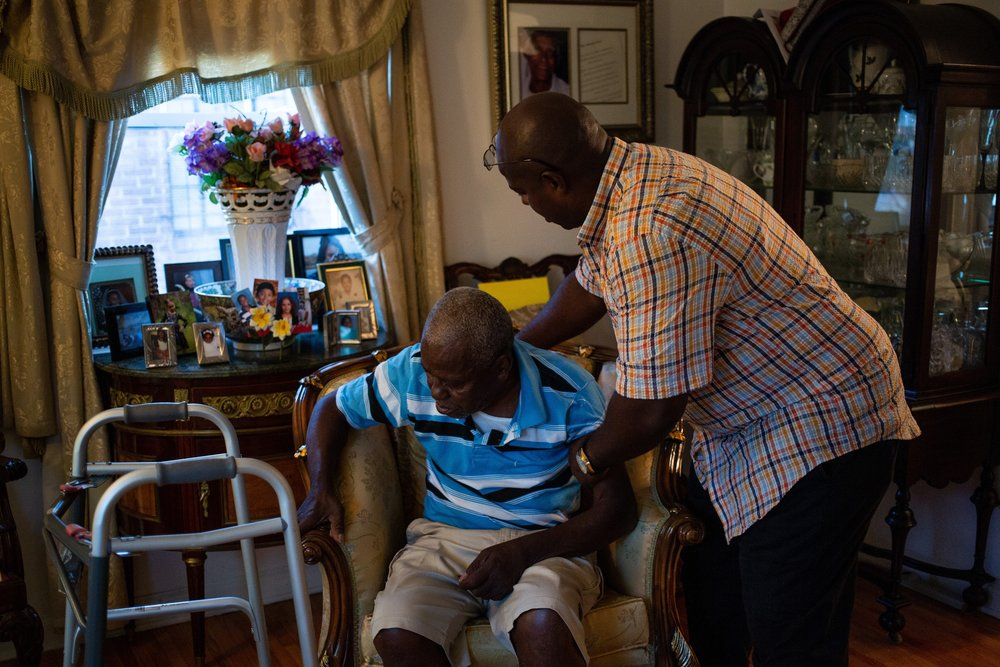 Danny Michel, right, helps his father, Paul Salim Michel, take a seat in the living room of MIchel's parents' home on Long Island. Photo: Ariel Zambelich | The Intercept