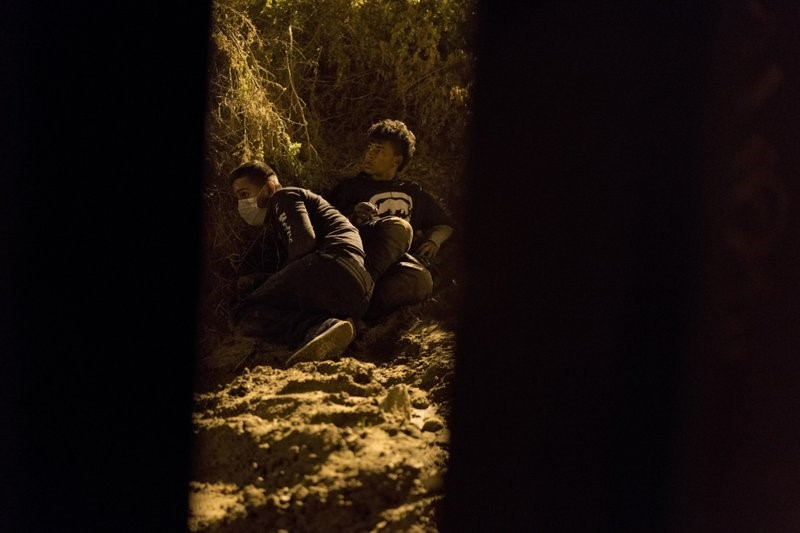 In this Friday, Nov. 30, 2018, file photo, Salvadoran migrant Cesar Jobet, right, and Daniel Jeremias Cruz, hide from U.S. border agents, after they dug a hole in the sand under the border structure and crossed over to the U.S. side, in Playas de Tijuana, Mexico. The two youths were detected by U.S. border agents and ran back to the Mexican side. Some immigrant youth looking to start over in the United States after fleeing abusive homes are seeing their applications for green cards rejected because the Trump administration says they're too old. A program in place since 1990 has let young immigrants file paperwork before age 21. But the U.S. government says some of these immigrants are too old once they turn 18. (AP Photo/Ramon Espinosa, File)