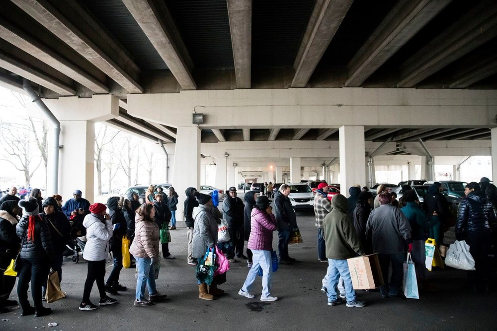 Furloughed federal workers and family members who were affected by the partial government shutdown waited in line on Jan. 23, 2019, to receive food distributed by volunteers in Philadelphia. (Matt Rourke/AP)