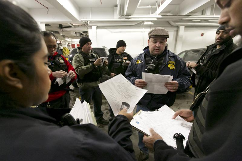 In this March 2, 2015 photo, Immigration and Customs Enforcement officers meet in the garage of a New York federal building, as they prepare for a series of early-morning arrests.  ( AP Photo )