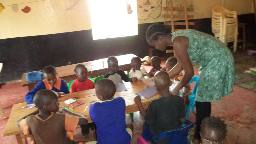 Children crayoning at the Faraja Center hall