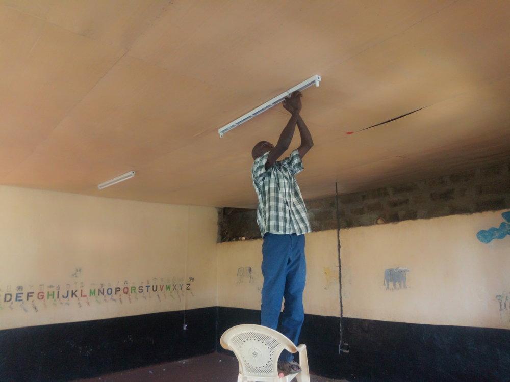 Elias fitting a florescent bulb holder