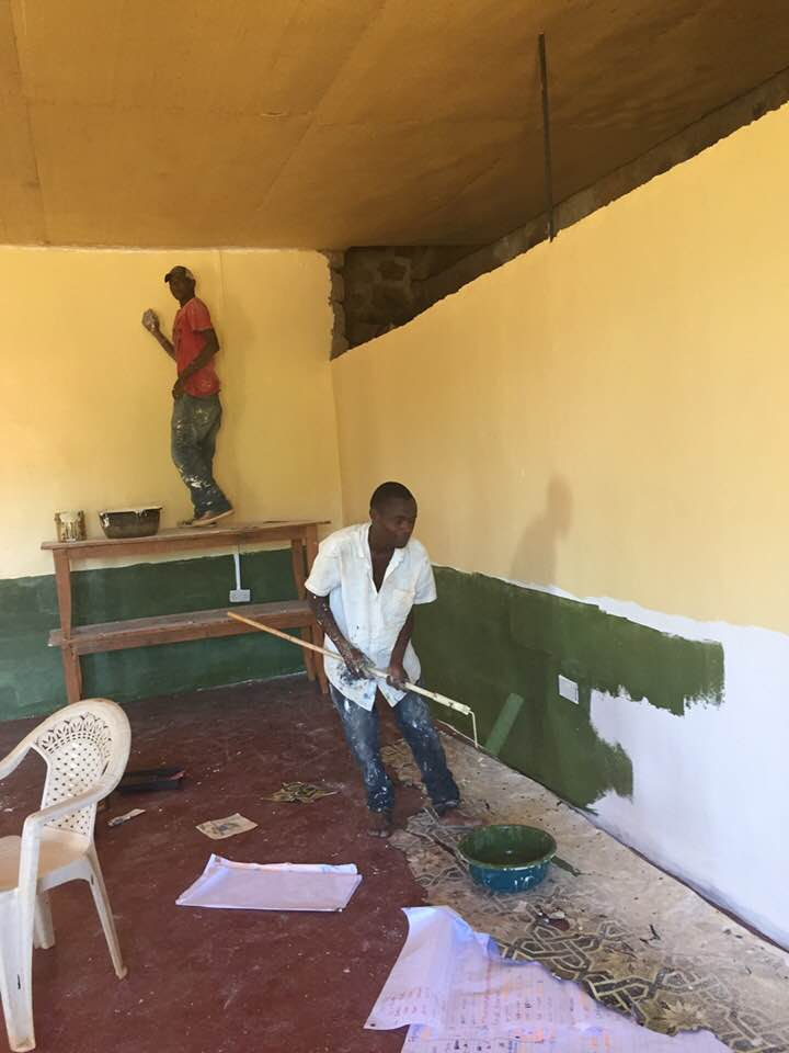Collins and Marcos painting the dark green and cream colours on the walls