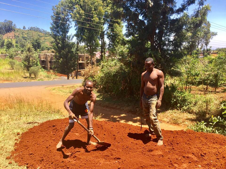 Guys leveling the soil from the soak pit.