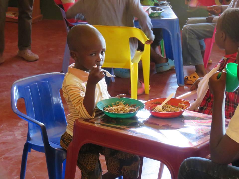 Kids enjoying spaghetti.