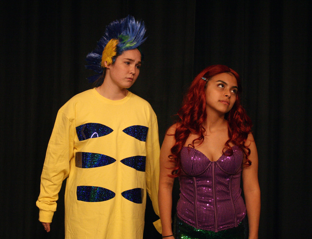Flounder (Sydney Suits) wishes that Ariel (Jennifer Trejo Benitez) would look at him the way she looks at the human prince.