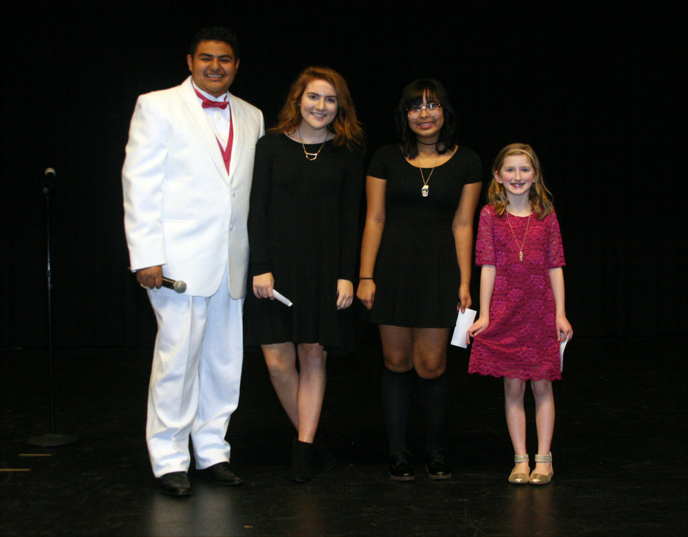 Master of ceremonies Orlando Balderas, from left, stands with Sing and Play '18 winners Corrine Collison, Edith Soto and Kaitlyn Evans. Registration is now open for Sing and Play '19, which will be held in February at Jordan-Matthews High School.