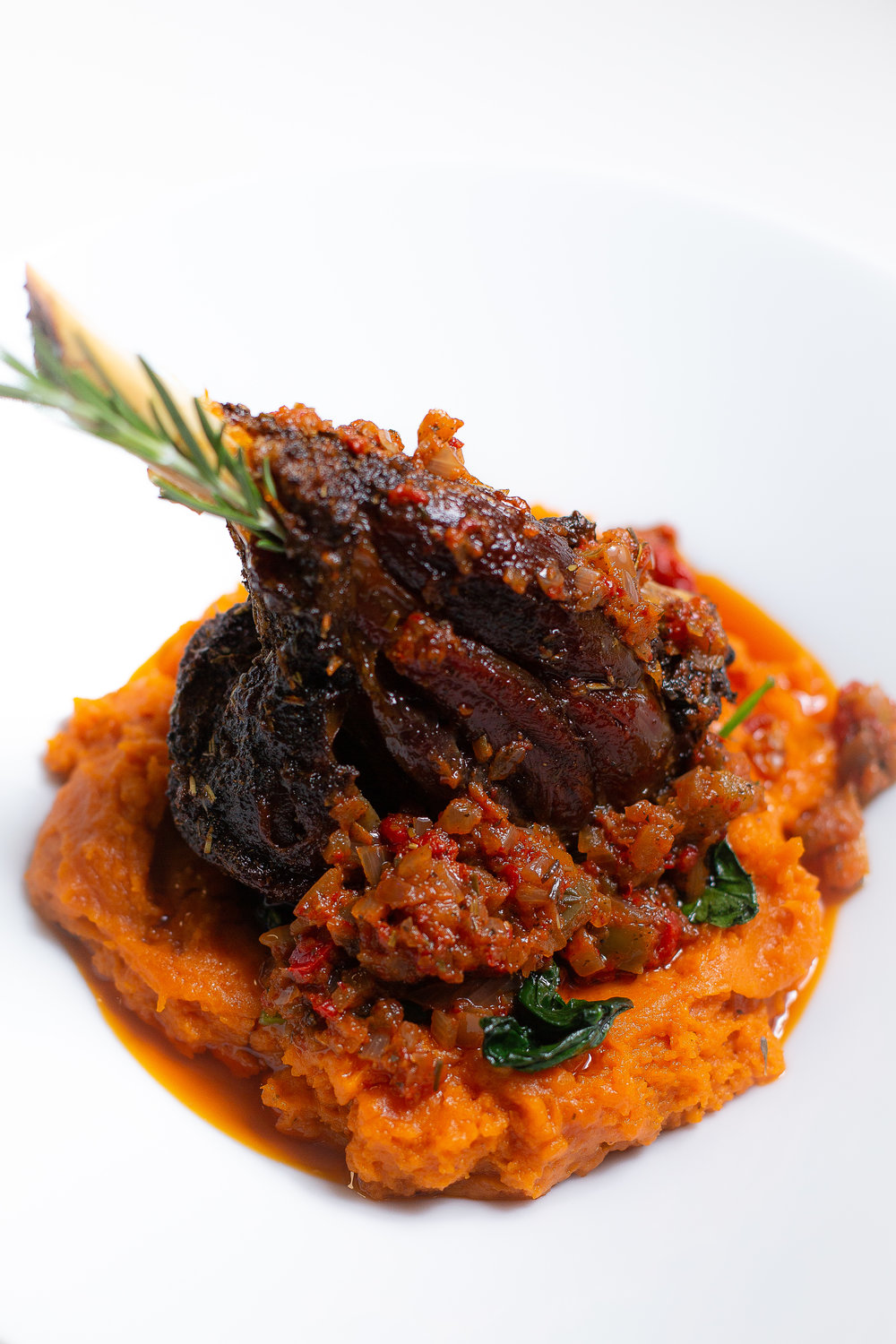 Braised Lamb Shank on a bed of sauteed spinach and yam cottage puree
