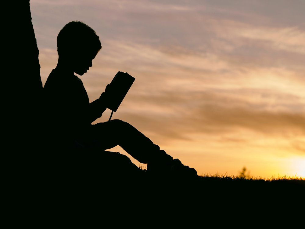 negative-space-silhouette-child-reading-sunset-aaron-burden.jpg