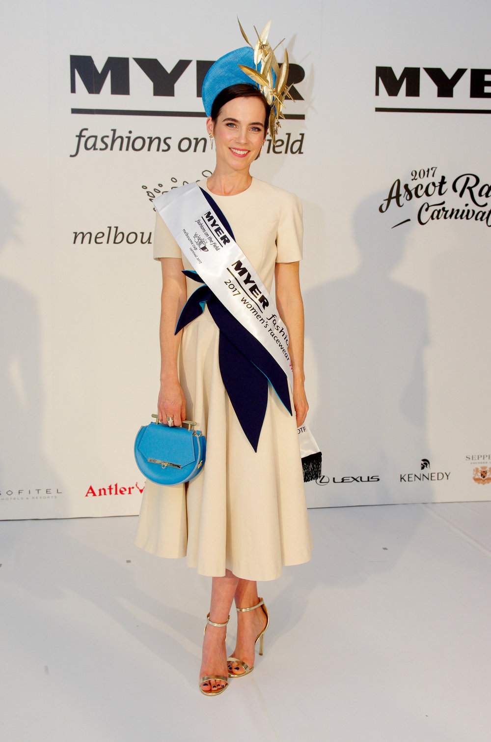 Elizabeth Winlo (Nee Pollard) who won the National Myer FOTF in 2009 looked stunning in this bone coloured linen dress with navy and bright blue detail. Her Millinery is by Reny Kestel and her bag was made in the USA.
