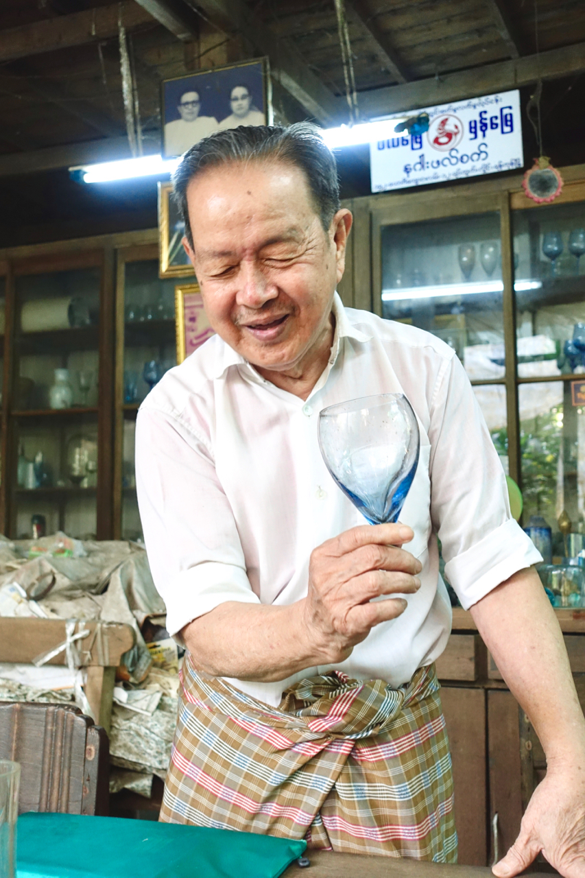 - U Thein Zavy cheerfully explains the history of a stemless wine glass, crafted at his families glass factory, Nagar Glass Factory in Yangon Myanmar.