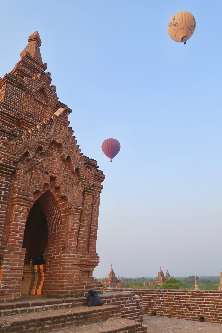 - Hot air BALLOONS FLOAT OVER A TEMPLE DURING SUNSET IN BAGAN MYANMAR