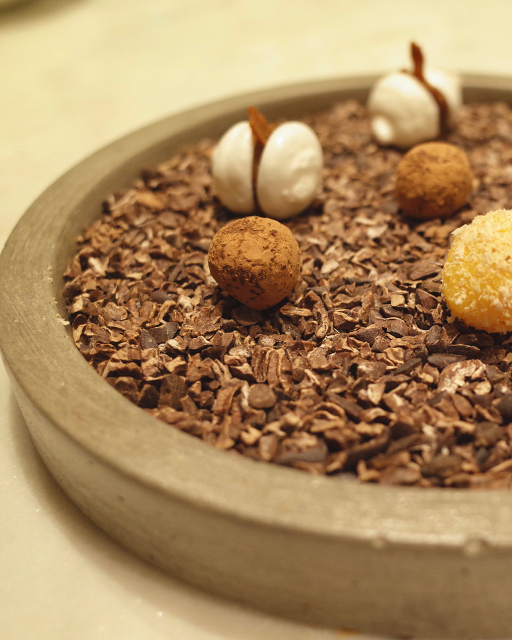 - Bite size chocolate truffles filled with pili nut butter, home made yema and micro meringues with a miso caramel.