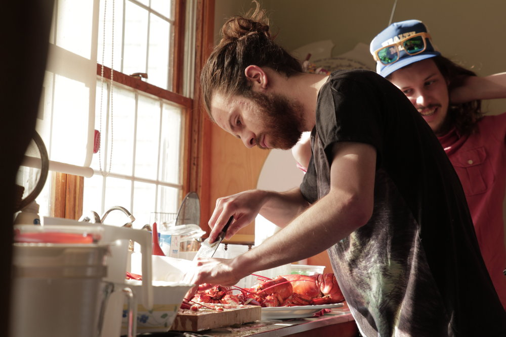 68. - As a gift, one of the families we were staying with offered us a crazy lobster feast. We got to cook them ourselves. Here is Collin, in his element as a chef.